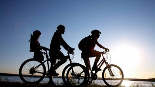 8936357 - young family go for a cycle ride on the beach at background sunset